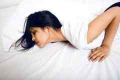 De vrij donkerbruine vrouw in bed, schuint slaap af Stock Foto's