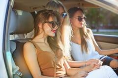 De vrij Europese meisjes 25-30 jaar oud in de auto maken foto op mobiele telefoon Stock Foto's