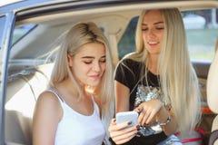 De vrij Europese meisjes 25-30 jaar oud in de auto maken foto op mobiele telefoon Royalty-vrije Stock Afbeeldingen
