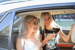 De vrij Europese meisjes 25-30 jaar oud in de auto maken foto op mobiele telefoon Stock Fotografie