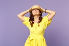 De vrij glimlachende jonge vrouw in gele kleding, de zomerhoed die ogen houden sloot, zettend handen op hoofd dat op pastelkleur  stock foto
