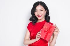 De vrij jonge Aziatische vrouw kleedde zich in rode kleding met een heden Royalty-vrije Stock Foto