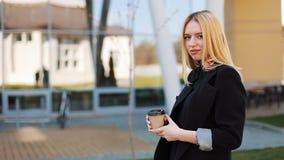 De vrij jonge blondevrouw bevindt zich met een buiten kop van koffie vóór een spiegelmuur stock video