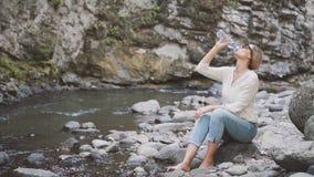 De vrij jonge blondevrouw in vrijetijdskleding, naakte voeten in water van snelle duidelijke rivier, dame op grote steen en opent stock video