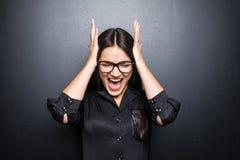 De vrij jonge boze vrouw in glazen die en op zwarte achtergrond gillen zweren Emotiesconcept stock foto's