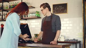 De vrij jonge dame koopt meeneemcoffe in koffie-winkel en betaalt met smartphone verrichtend betaling zonder contact modern stock videobeelden
