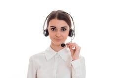 De vrij jonge donkerbruine vrouw van de vraagbeambte met hoofdtelefoons en microfoon die die de camera bekijken op wit wordt geïs Stock Afbeelding
