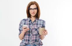 De vrij jonge smartphone van de vrouwenholding, die apparaat met behulp van, die modieuze glazen, glimlachen dragen, geïsoleerd o stock afbeeldingen