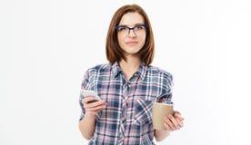 De vrij jonge smartphone van de vrouwenholding, die apparaat met behulp van, die modieuze glazen, het glimlachen dragen, die een  royalty-vrije stock foto's