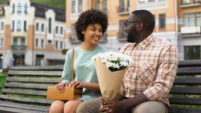 De vrij jonge vriend van de damevergadering op eerste datum, mens die witte bloemen voorstellen stock video