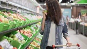 De vrij jonge vrouw kiest fruit in kruidenierswinkelopslag, raakt zij en ruikt appelen dan zettend hen in karretje stock videobeelden