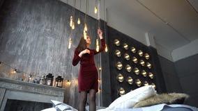 De vrij jonge vrouw in kleding die zich op bed bevinden en stelt in studio stock videobeelden