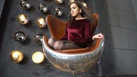 De vrij jonge vrouw in kledingszitting op leunstoel en stelt in studio stock video