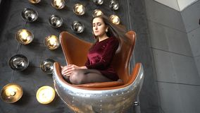 De vrij jonge vrouw in kledingszitting op leunstoel en stelt in studio stock footage
