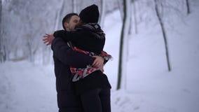De vrij jonge vrouw lanceert aan de kerel en springt in zijn wapens in de winterpark Een mens neemt zijn meisje op, koesteren zij stock video