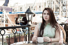 De vrij jonge vrouw met donker lang haar en blauwe ogen zit in caf Royalty-vrije Stock Fotografie