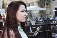 De vrij jonge vrouw met donker lang haar en blauwe ogen zit in caf Royalty-vrije Stock Foto's