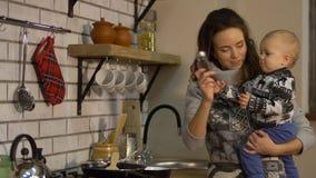 De vrij jonge vrouw met een baby die in haar wapens in moderne keuken ontbijtdame voorbereiden giet zout in de pan stock video