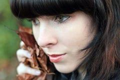 De vrij jonge vrouw met in hand gebladerte Stock Fotografie