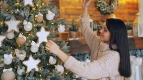 De vrij jonge vrouw verfraait Kerstboom wat betreft ballen en speelgoed en glimlacht genietend van vakantie en feestelijk stock video
