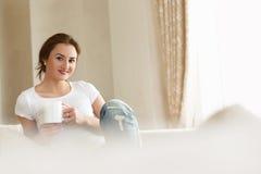 De vrij jonge vrouw witte t-shirt dragen en de jeans die houden een kop van coffeeandglimlach terwijl het zitten op de leunstoel Royalty-vrije Stock Fotografie