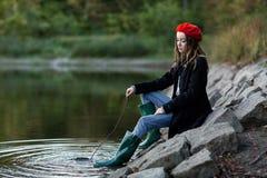 De vrij jonge vrouw zit bij een vijver Stock Afbeelding