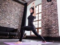 De vrij jonge vrouwelijke atleet in het zwarte sportenuitrusting doen valt oefening of status in yoga uit de lage strijder op mat stock afbeelding