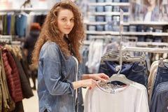 De vrij jonge vrouwelijke klant met krullend haar, draagt denimjasje, kiest nieuwe sweater, stelt tegen grote opslagachtergrond m royalty-vrije stock afbeelding