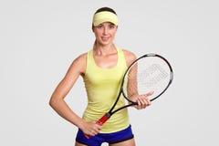 De vrij jonge vrouwelijke speler dierbaar van tennis, houdt racket, klaar om winnaar te raken en balsprong te laten, draagt gele  stock foto's