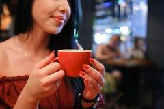 De vrij jonge vrouwelijke vrouw houdt in hand kop en drinkt coffee ag royalty-vrije stock afbeeldingen