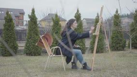 De vrij jonge zitting van de meisjesschilder voor houten schildersezel die een beeld trekken De vrouwelijke kunstenaar in het toe stock video