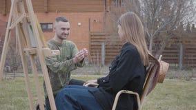 De vrij jonge zitting van de vrouwenschilder voor houten schildersezel in openlucht De gelukkige mens zette de ring op de vinger  stock footage
