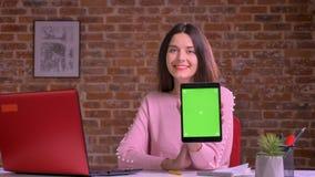 De vrij Kaukasische bedrijfsvrouw toont het groene scherm en glimlacht gelukkig en ontspande bij het bureau naast de bakstenen mu stock footage
