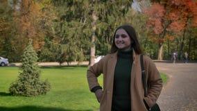 De vrij Kaukasische vrouw loopt op zonnig stedelijk gebied en vawing met leuke glimlach, de herfst vibes, groene achtergrond, mot stock videobeelden