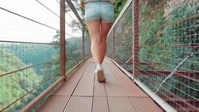 De vrij sexy slanke dame in toevallige lichte de zomerkleren, meisje met blond verzameld haar loopt langzaam langs een houten luc stock footage