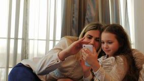 De vrije tijd van de de zorgfamilie van de moederliefde het doorbladeren telefoon stock video