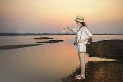 De vrijetijdskleding die van de reizigersslijtage bij zonsondergang op stil meer ontspannen stock afbeelding