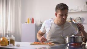 De vrijgezel bereidde untasty soep, weerzinwekkend met geur van maaltijd, beginnerchef-kok voor stock videobeelden