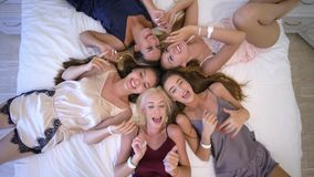 De vrijgezellin van de huispartij, grappige en gelukkige meisjes met mooie make-up in aardige pyjama's die en het liggen op bed z stock video