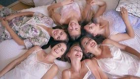 De vrijgezellinpartij, schitterend glimlachend vriendenmeisje in zijdepyjama's ligt op bed en onderzoekt de camera in flat stock videobeelden