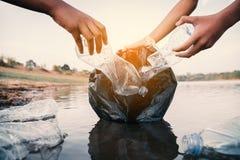 De vrijwilliger die een flessenplastiek in de rivier opnemen stock fotografie