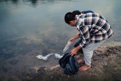 De vrijwilliger die een flessenplastiek in de rivier opnemen stock foto's
