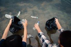 De vrijwilliger die een flessenplastiek in de rivier opnemen stock afbeeldingen