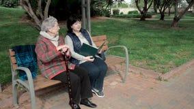 De vrijwilliger leest boek voor bejaardezitting op een bank in een stadspark stock video