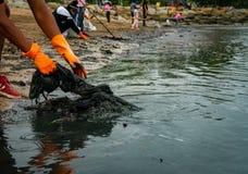 De vrijwilligers dragen oranje rubberhandschoenen om huisvuil op het strand te verzamelen De verontreiniging van het strandmilieu stock foto's
