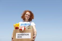 De vrijwilligers dragende doos van de voedselschenking Stock Afbeelding