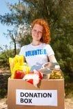 De vrijwilligers dragende doos van de voedselschenking Stock Foto's