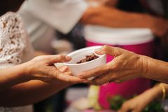 De vrijwilligers verstrekken voedsel voor bedelaars: Concepten het Voeden en hulp: Concept voedsel die voor de armen delen om hon stock afbeeldingen
