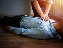 De vrijwilligerspomp van de het gebruikshand van de bureauvrouw op borst voor eerste hulpnoodsituatie CPR op onbewuste hartaanval stock afbeeldingen