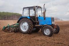 In de vroege, de lenteochtend, gaat de tractor en trekt een ploeg, die een gebied ploegen alvorens van gewassen te landen Stock Foto